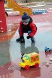 Niño que juega con los coches del juguete Foto de archivo