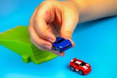 Niño que juega con los coches micro de la velocidad nana en fondo azul Fotografía de archivo libre de regalías