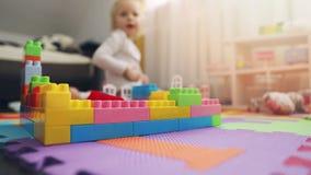 Niño que juega con los juguetes en su sitio metrajes