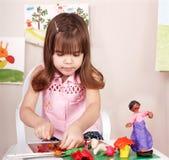 Niño que juega con plasticine en escuela. Fotografía de archivo libre de regalías