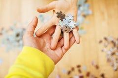Niño que juega con rompecabezas en piso de madera así como el padre, concepto de la gente de la forma de vida, manos cariñosas a  Imagen de archivo libre de regalías