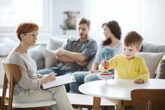 Ni?o que juega con terapia superior de giro ADHD con los padres imágenes de archivo libres de regalías