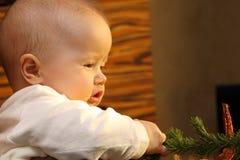Niño que juega con un árbol de navidad Imagen de archivo