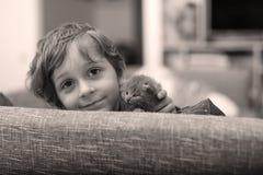 Niño que juega con un gatito Imagen de archivo libre de regalías