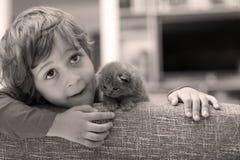 Niño que juega con un gatito Imagenes de archivo