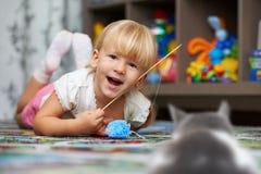 Niño que juega con un gato en el piso en el cuarto del ` s de los niños Imagen de archivo