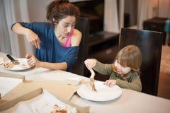 Niño que juega con un pedazo de la pizza con el mothe Imagenes de archivo