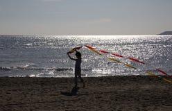 Niño que juega con una cometa en la playa en la puesta del sol Fotografía de archivo libre de regalías