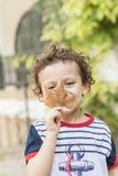 Niño que juega con una hoja de la caída del otoño imagenes de archivo