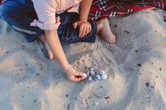Niño que juega conchas de berberecho fotografía de archivo