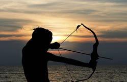 Niño que juega el arco y la flecha en la playa, silueta Fotos de archivo libres de regalías