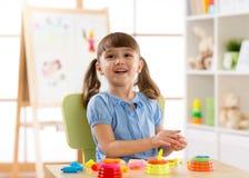 Niño que juega el plasticine en jardín de la infancia fotos de archivo