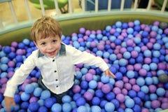 Niño que juega en caja con las bolas fotografía de archivo