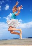 Niño que juega en el cielo azul del aganiist de la playa. Imagen de archivo