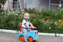 Niño que juega en el coche del juguete imagen de archivo