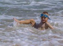 Niño que juega en el océano Fotografía de archivo libre de regalías