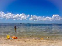 Niño que juega en el océano Foto de archivo