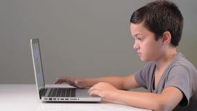 Niño que juega en el ordenador y el teléfono en casa almacen de video