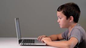 Niño que juega en el ordenador y el teléfono en casa metrajes