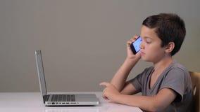 Niño que juega en el ordenador y el teléfono en casa almacen de metraje de vídeo
