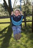 Niño que juega en el oscilación Fotos de archivo