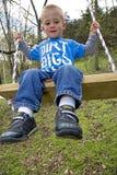 Niño que juega en el oscilación Foto de archivo libre de regalías