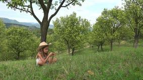 Niño que juega en hierba, muchacha que se relaja en la huerta al aire libre en la naturaleza, verano 4K