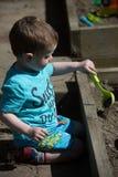 Niño que juega en hoyo de arena Fotografía de archivo libre de regalías
