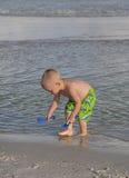 Niño que juega en la arena y la resaca. Imagenes de archivo