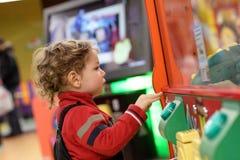 Niño que juega en la máquina de juego Imagenes de archivo