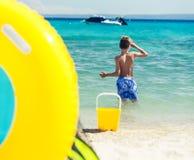 Niño que juega en la playa con los juguetes Imagen de archivo