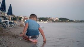 Niño que juega en la playa Vacaciones de verano almacen de video