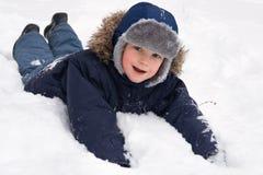 Niño que juega en nieve imagenes de archivo