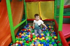 Niño que juega en piscina de la bola imagen de archivo libre de regalías