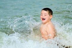 Niño que juega en resaca en la playa Foto de archivo