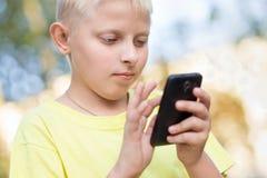 Niño que juega en su smartphone Imagen de archivo libre de regalías