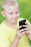 Niño que juega en su smartphone Imagen de archivo