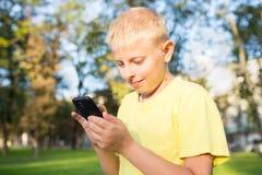 Niño que juega en su smartphone Foto de archivo libre de regalías