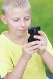 Niño que juega en su smartphone Imagenes de archivo