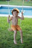Niño que juega en un oscilación Fotos de archivo