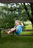 Niño que juega en un oscilación Imagen de archivo libre de regalías