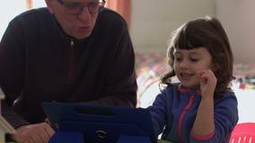 Niño que juega en una tableta que bromea con el papá SF almacen de metraje de vídeo