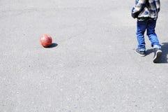 Niño que juega a fútbol en el asfalto, jugador de equipo de fútbol, entrenando a forma de vida al aire libre, activa Imágenes de archivo libres de regalías