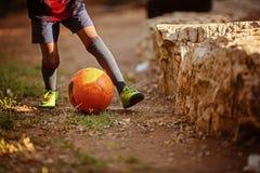 Niño que juega a fútbol en la playa Fotografía de archivo
