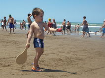 Niño que juega la bola en la playa Foto de archivo libre de regalías