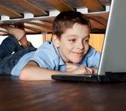 Niño que juega la computadora portátil bajo la cama Foto de archivo libre de regalías