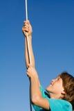 Niño que juega la cuerda que sube Imagen de archivo libre de regalías