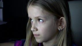 Niño que juega la PC de la tableta en la noche, Internet de observación de la muchacha en el ordenador portátil en 4K oscuro almacen de metraje de vídeo