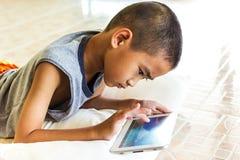 Niño que juega la tableta 03 fotografía de archivo