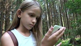 Niño que juega la tableta al aire libre en acampar, uso Smartphone del niño en el bosque, opinión de la muchacha metrajes
